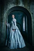 stock photo of gothic female  - Woman in victorian dress imprisoned in a dungeon