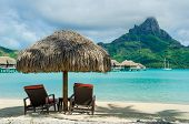stock photo of pacific islands  - Two sunlounger chairs under a thatched parasol on a white sand beach with a view on the lagoon and the tropical island of Bora Bora near Tahiti in French Polynesia - JPG