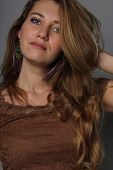 image of neutral  - studio portrait of the thoughtful young girl close up with a long fair hair of 25 years in a brown blouse on a neutral background the hand in hair - JPG