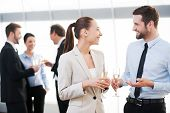stock photo of office party  - Two cheerful business people drinking champagne and talking while other people communicating in the background - JPG