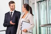stock photo of elevator  - Two cheerful business people discussing something and smiling while getting out from elevator