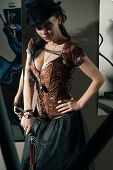 picture of bosoms  - Girl with vintage gun in steampunk style standing near the mirror - JPG