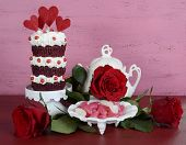 stock photo of red velvet cake  - Vintage style triple layer red velvet cupcake on white cake stand with roses and candy against a vintage shabby chic pink and red wood background - JPG