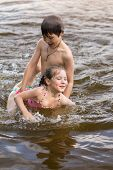 picture of little sister  - Little boy teaches his little sister to swim in a lake - JPG