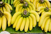 image of bunch bananas  - Closeup Bunch of yellow bananas on green banana leaf - JPG