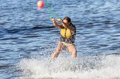 foto of watersports  - Young Woman riding the wakeboard on a lake - JPG