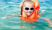picture of sea life  - Smiling little girl swimming with life jacket in the sea - JPG