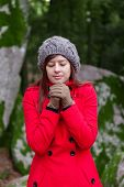 picture of overcoats  - Young woman shivering with cold on a forest wearing a red overcoat - JPG