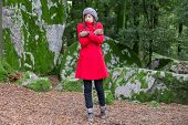 picture of overcoats  - Young woman shivering with cold and embracing herself on a forest wearing a red overcoat - JPG
