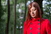 picture of overcoats  - Young woman feeling sad walking on a forest wearing a red overcoat during winter under a sunlight ray - JPG