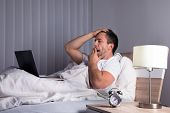 picture of yawning  - Portrait Of A Sleepy Man Yawning On Bed Looking At Laptop - JPG