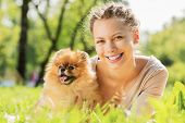 image of dog park  - Young pretty girl in summer park with cute dog - JPG