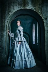 stock photo of gothic hair  - Woman in victorian dress imprisoned in a dungeon  - JPG