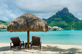 stock photo of french polynesia  - Two sunlounger chairs under a thatched parasol on a white sand beach with a view on the lagoon and the tropical island of Bora Bora near Tahiti in French Polynesia - JPG