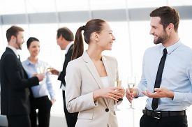 stock photo of mature adult  - Two cheerful business people drinking champagne and talking while other people communicating in the background - JPG