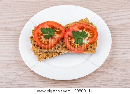 Crisp Bread With Slice Of Tomatoes In Plate On Table