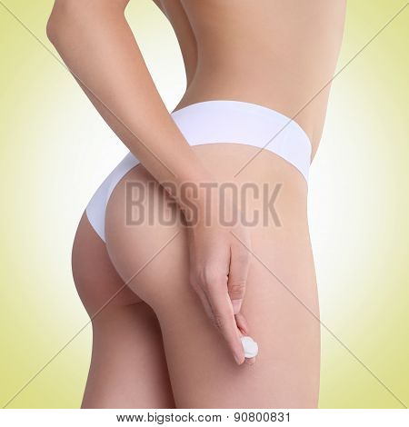 Woman Applying Cosmetic Cream From Cellulite On The Buttocks