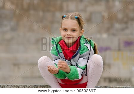 Six Year Old Girl Crouched On The Background Of A Granite Wall