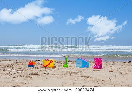 Colorful Plastic Beach Toys Lying On The Beach Sand