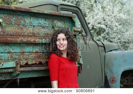 Blue-eyed brunette standing near truck body with peeling robin egg blue color paint