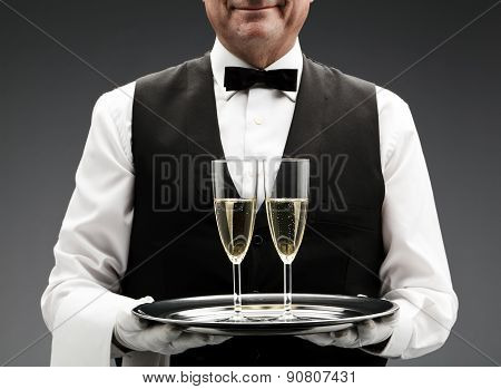 butler with two champagne flutes