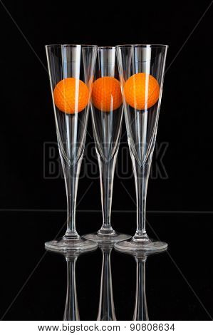 Three Glasses Of Champagne With  Orange Golf Balls