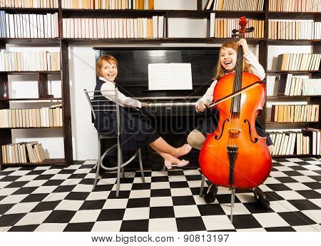 Girls playing on violoncello and the piano