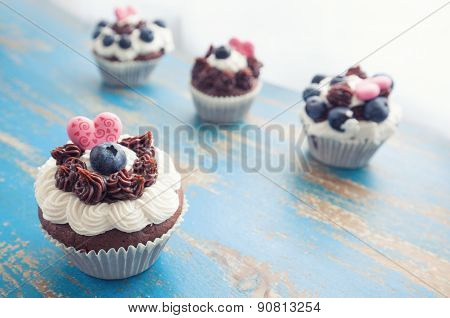 Decorated Cupcakes On Rustic Blue Table Top