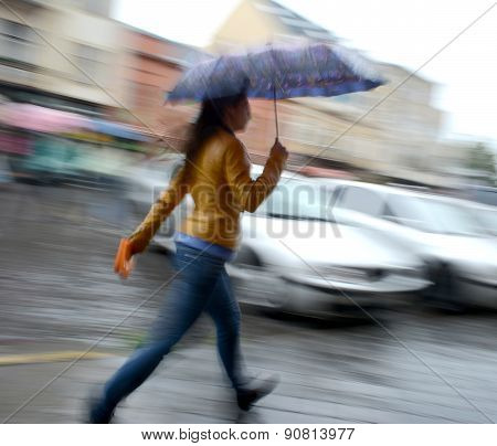 Woman Walking Down The Street On A Rainy Day