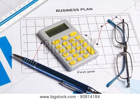 Close Up Of Business Plan With Graphs, Charts And Calculator