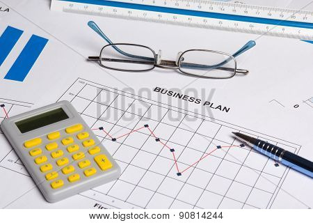 Close Up Of Business Plan With And Calculator