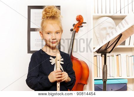 Cute blond girl with flute standing near cello