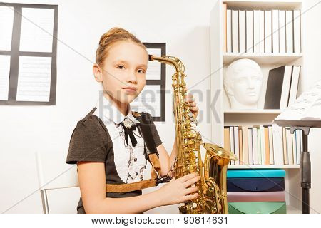 Portrait of girl in dress with alto saxophone
