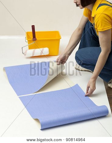 Woman unrolling wallpaper