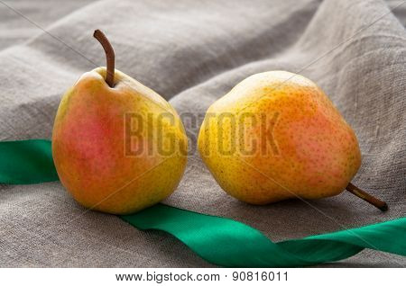Art still life with small red pears and green ribbonon hessian linen fabric cloth background