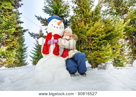 Girl and snowman with scarf together in forest