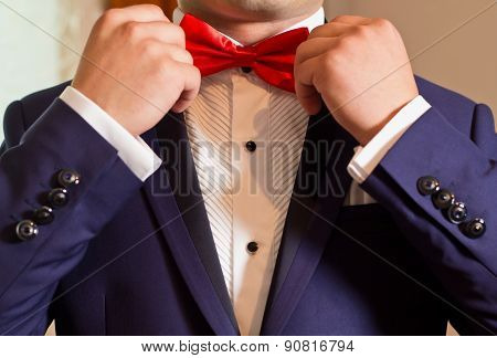 Groom In A White Shirt And Blue Suit Correcting bow tie