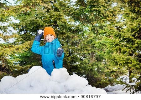 Happy boy in blue winter jacket playing snowballs