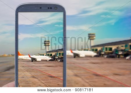 Smatrphone and airport background. Idea of taking shots, accessing apps, Internet, blogs and others. The blur image is an airport scene with airplane landed and another taxing for taking off.