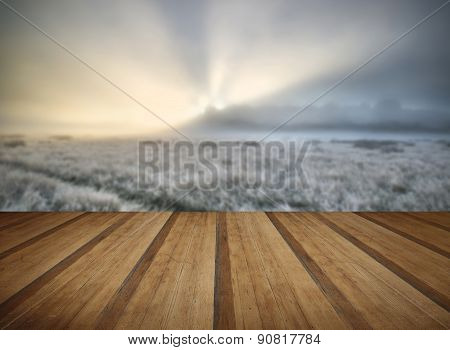 Stunning Sun Beams Light Up Fog Through Thick Fog Of Autumn Fall Frosty Landscape With Wooden Planks