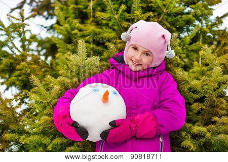 Smiling girl holding snowman's head in forest