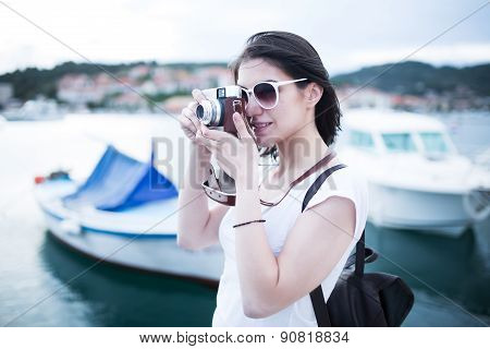 Attractive woman taking pictures with vintage retro camera laughing and smiling happy during holiday