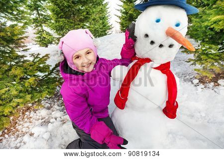 Close-up view of small girl and snowman in forest