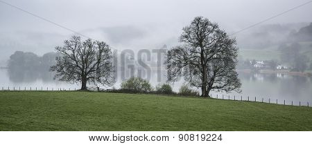 Misty Morning Landscape Over Lake Windermere In Lake District In England
