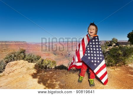 Happy boy bundled up in USA flag, Grand Canyon