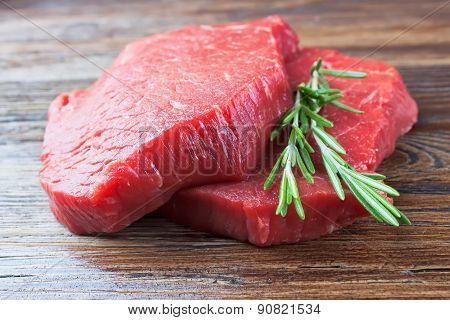 raw beef steak with rosemary