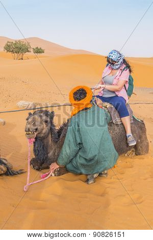 MERZOUGA, MOROCCO, APRIL 13, 2015: Local guide helps young tourist to get on a camel before an excursion into Dunes Erg Chebbi