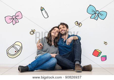 Portrait of happy young couple sitting against a white wall and dreaming to have a baby and a family. Their dreams are sketched with colors on the wall.
