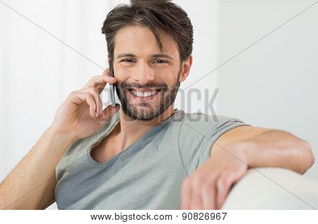 Portrait of smiling man talking on cellphone at home