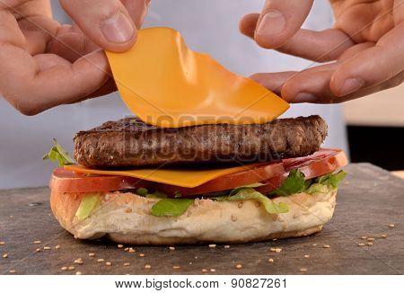 Cheddar cheese on burger.Preparing and making hamburger.